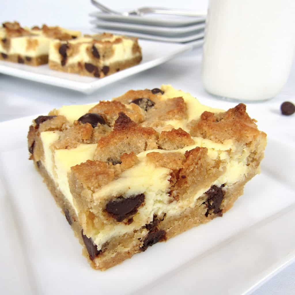 chocolate chip cheesecake bar slice on dish with platter in background