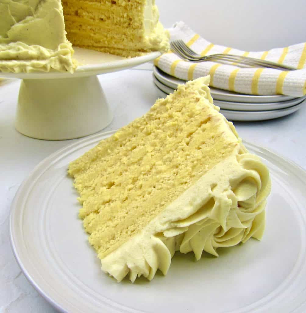 slice of lemon layer cake on white plate with cake in background