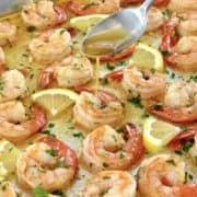garlic butter shrimp on baking sheet with butter spooned on top