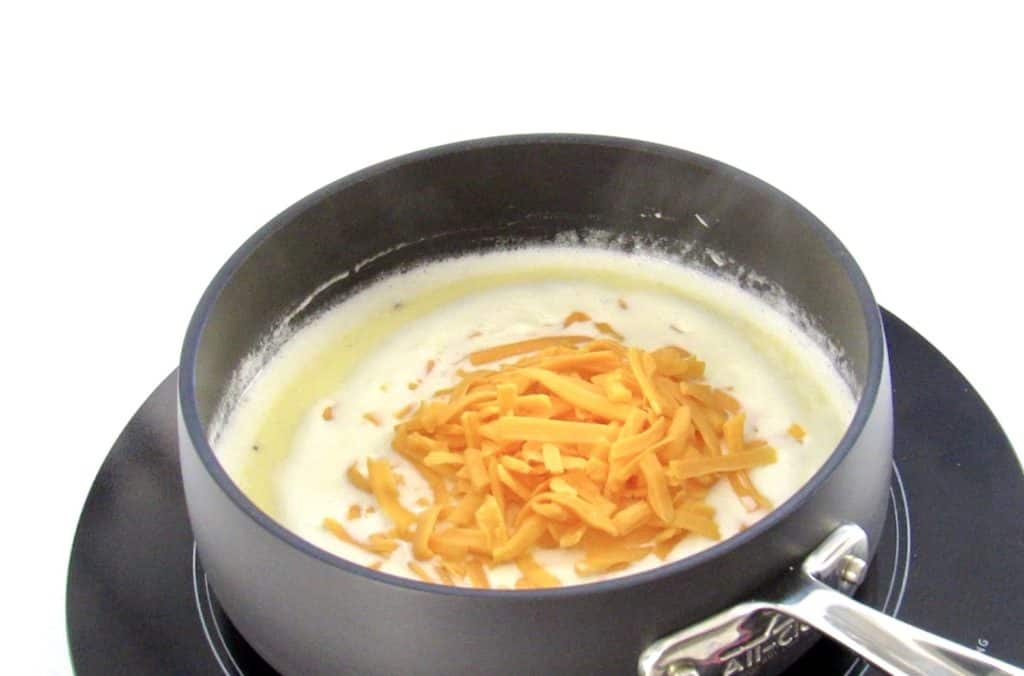 shredded cheese in heavy cream in a pan