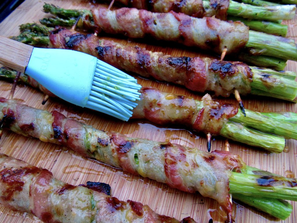 bacon wrapped asparagus being brushed with glaze