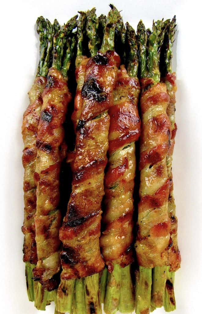 overhead view of Grilled Bacon Wrapped Asparagus on white plate