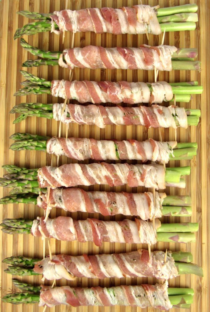asparagus wrapped in bacon with toothpicks on cutting board