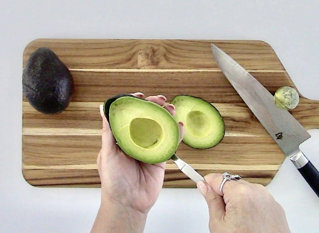 avocado being scooped out with a spoon