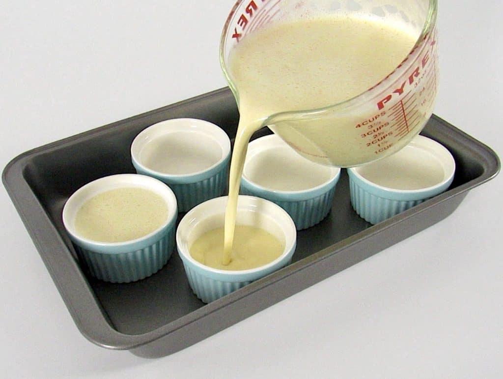 Keto Creme Brûlée mixture being poured into baking pan with ramekins
