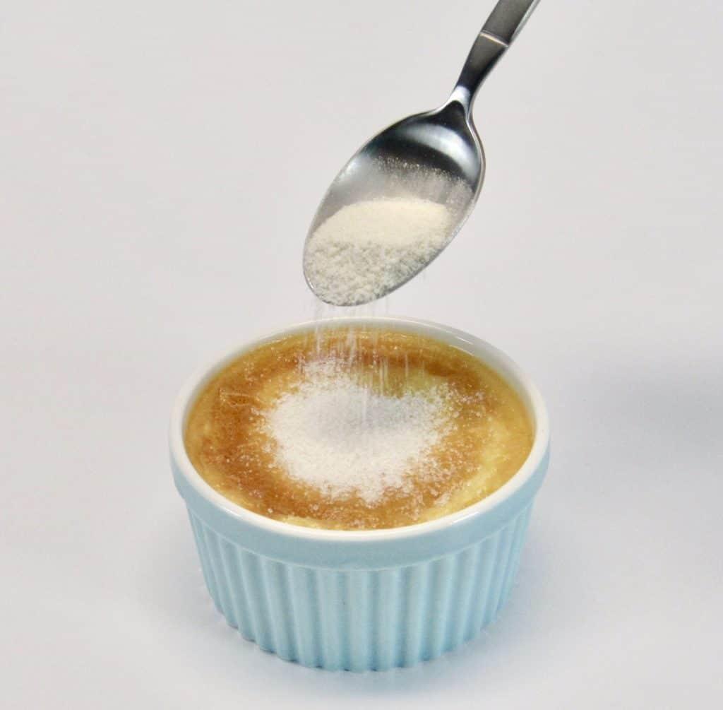 sugar being spooned over creme brûlée ramekin