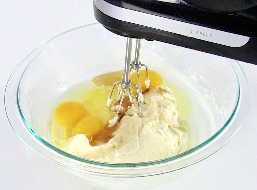 eggs with wet ingredients being mixed in glass bowl