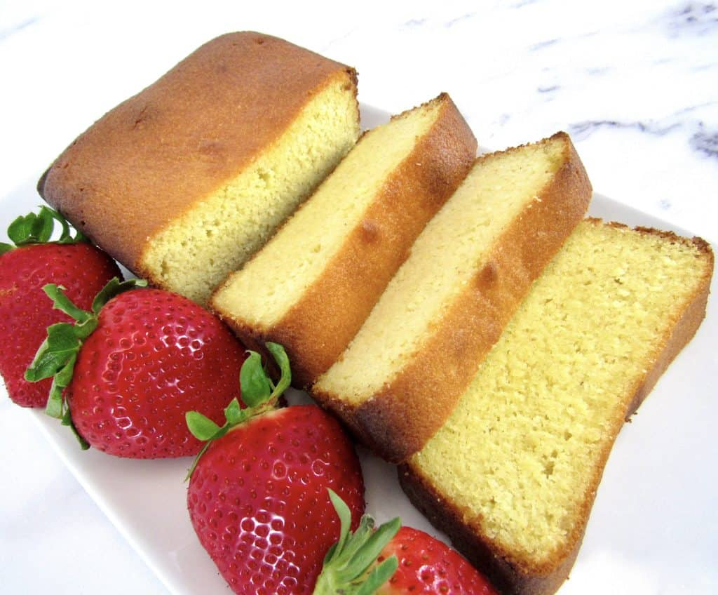 sliced pound cake on white plate with strawberries on side