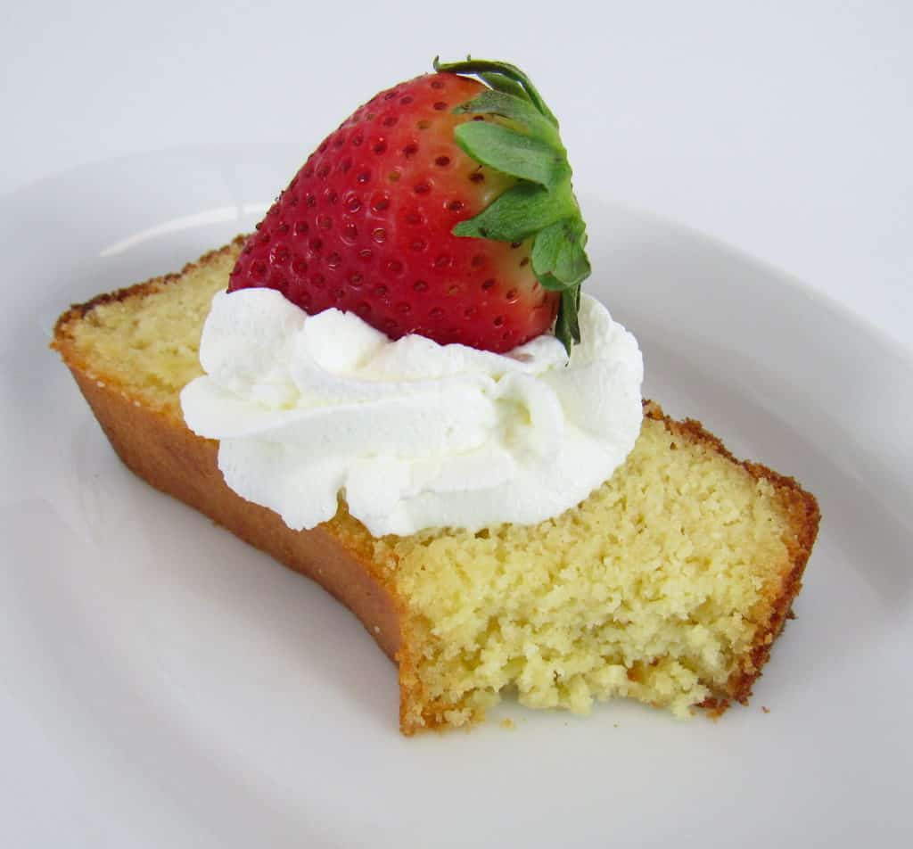 slice of pound cake with whip cream and a strawberry on top