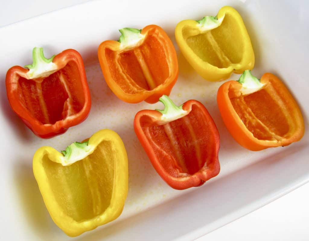 red yellow and orange peppers cut open in white casserole