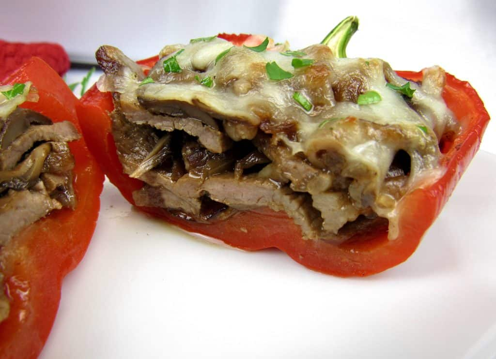baked stuffed red pepper on white plate cut open