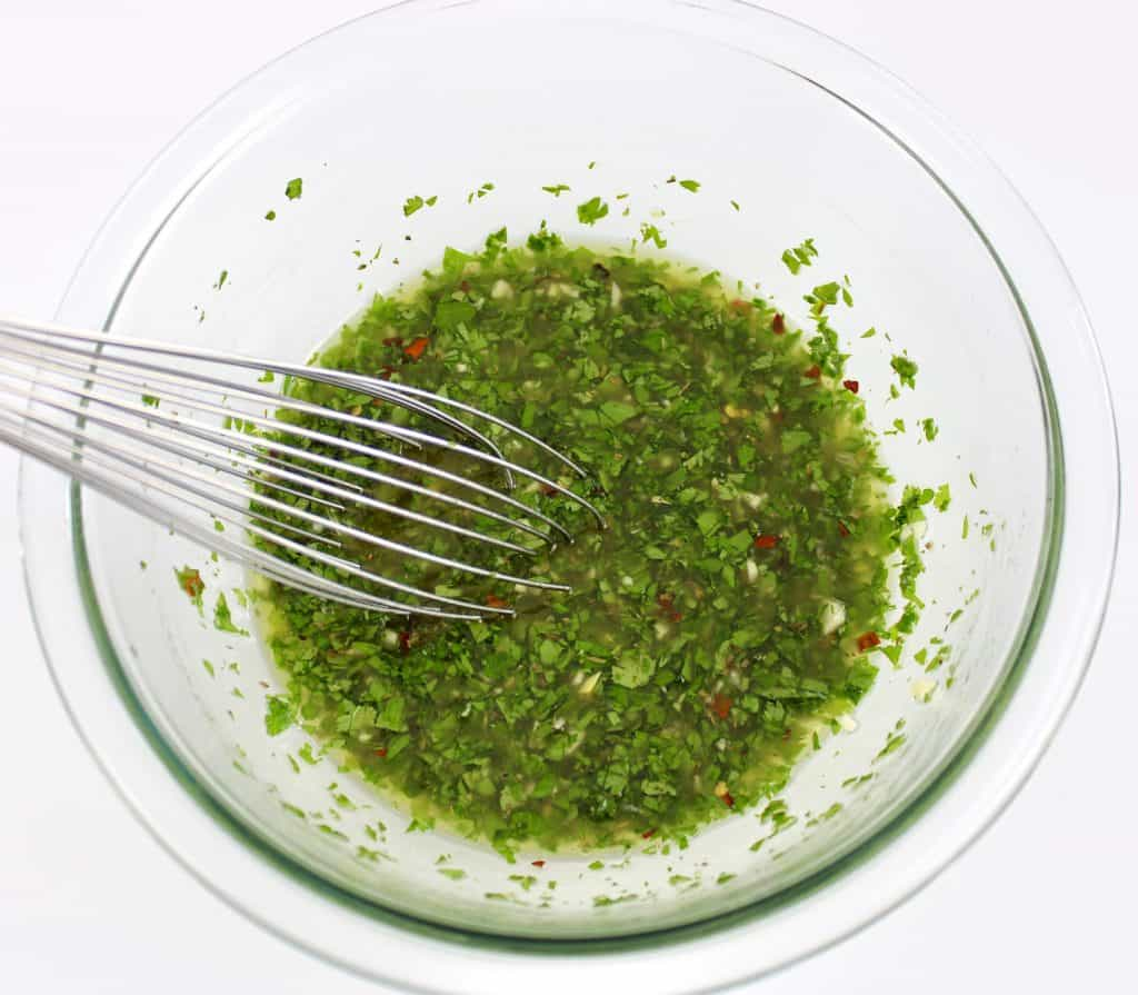chimichurri sauce being whisked in glass bowl
