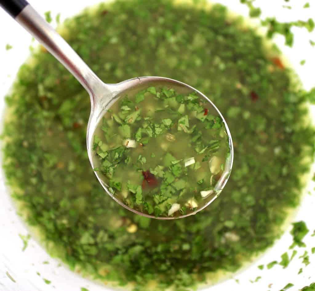 chimichurri sauce being spooned out of glass bowl