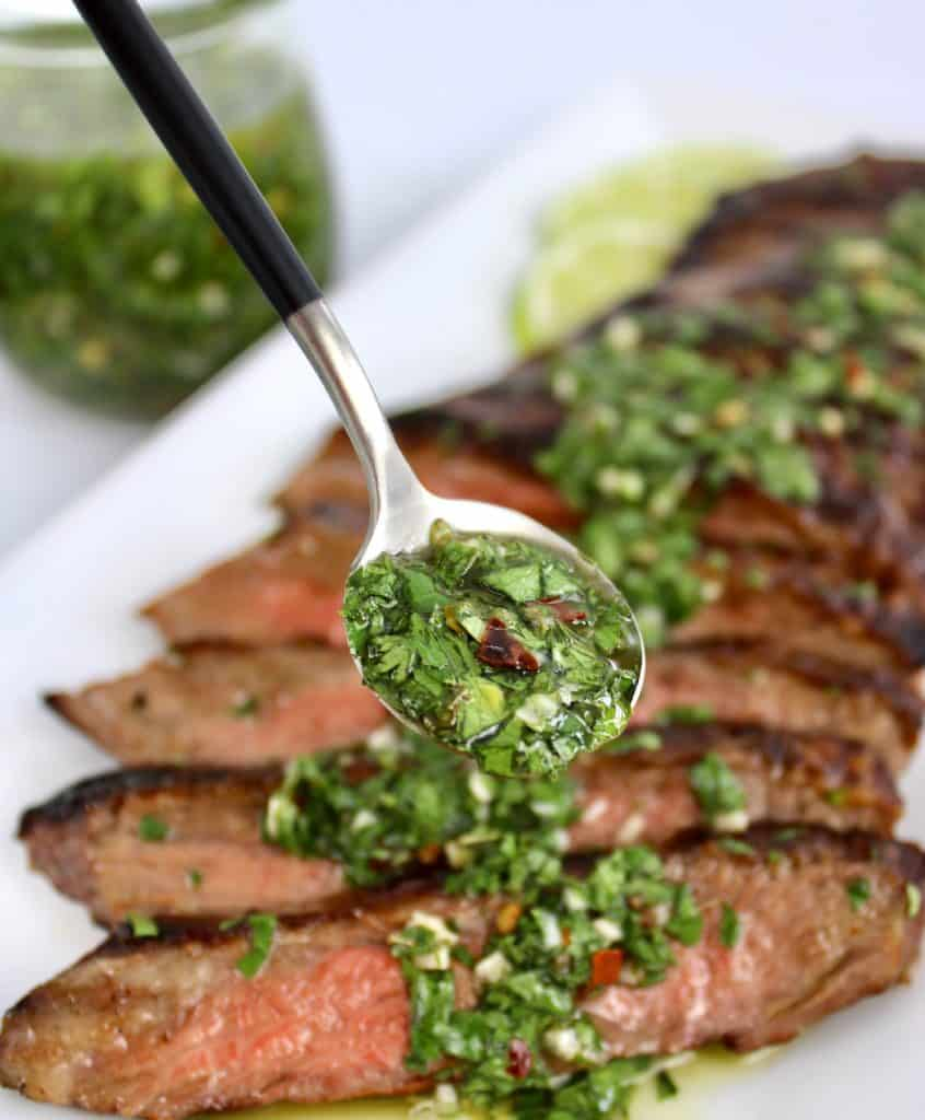 chimichurri sauce being spooned over slicked steak on white plate
