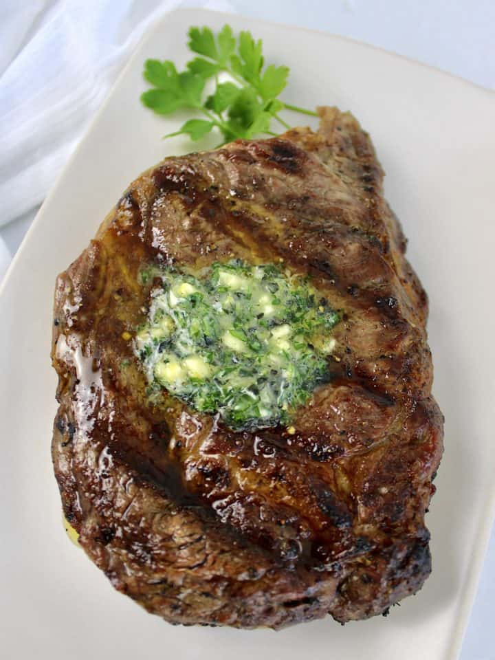 grilled ribeye steak with partially melted compound butter on top