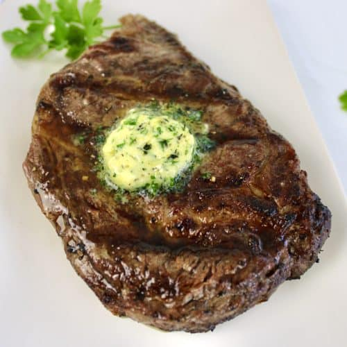 grilled ribeye steak with pad of compound butter on top