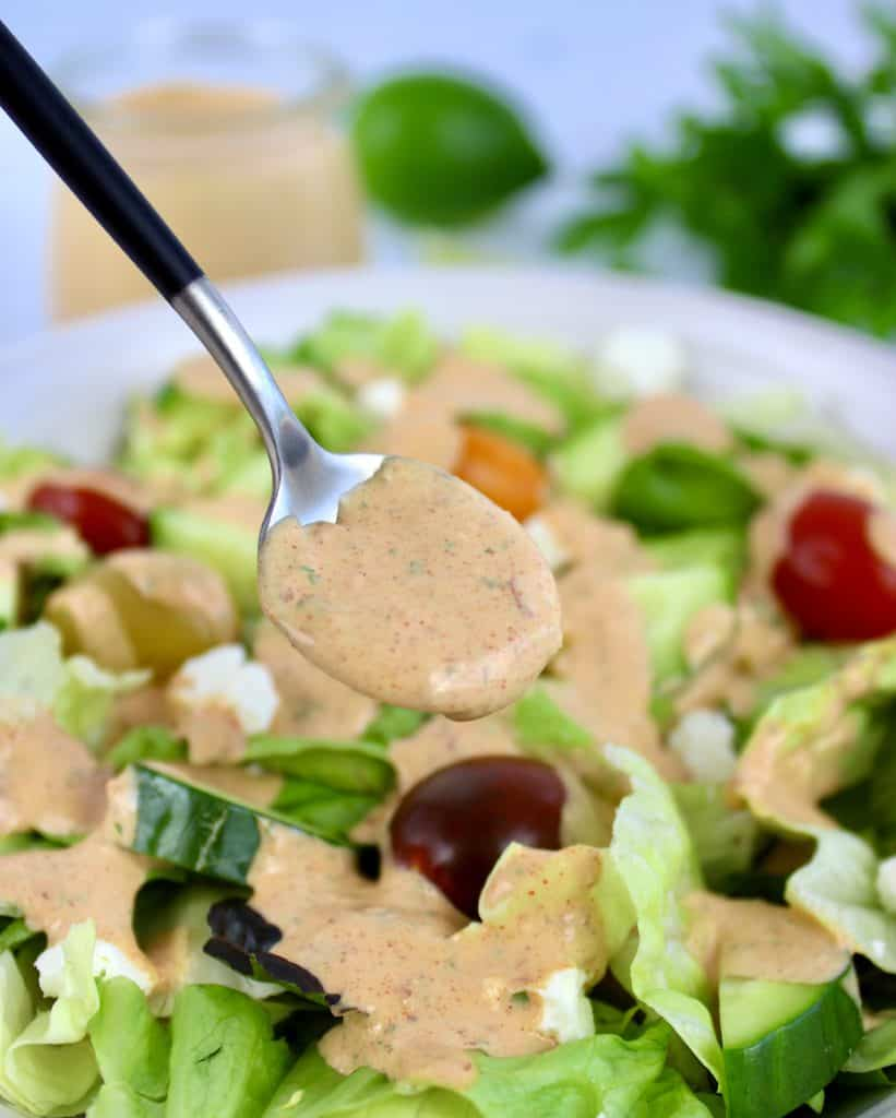 salad with chipotle ranch being spooned over the top