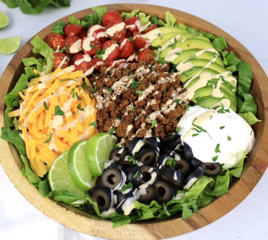 closeup of taco salad in wooden bowl with dressing drizzled on top