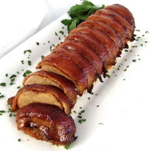Bacon Wrapped Pork Tenderloin on white plate sliced