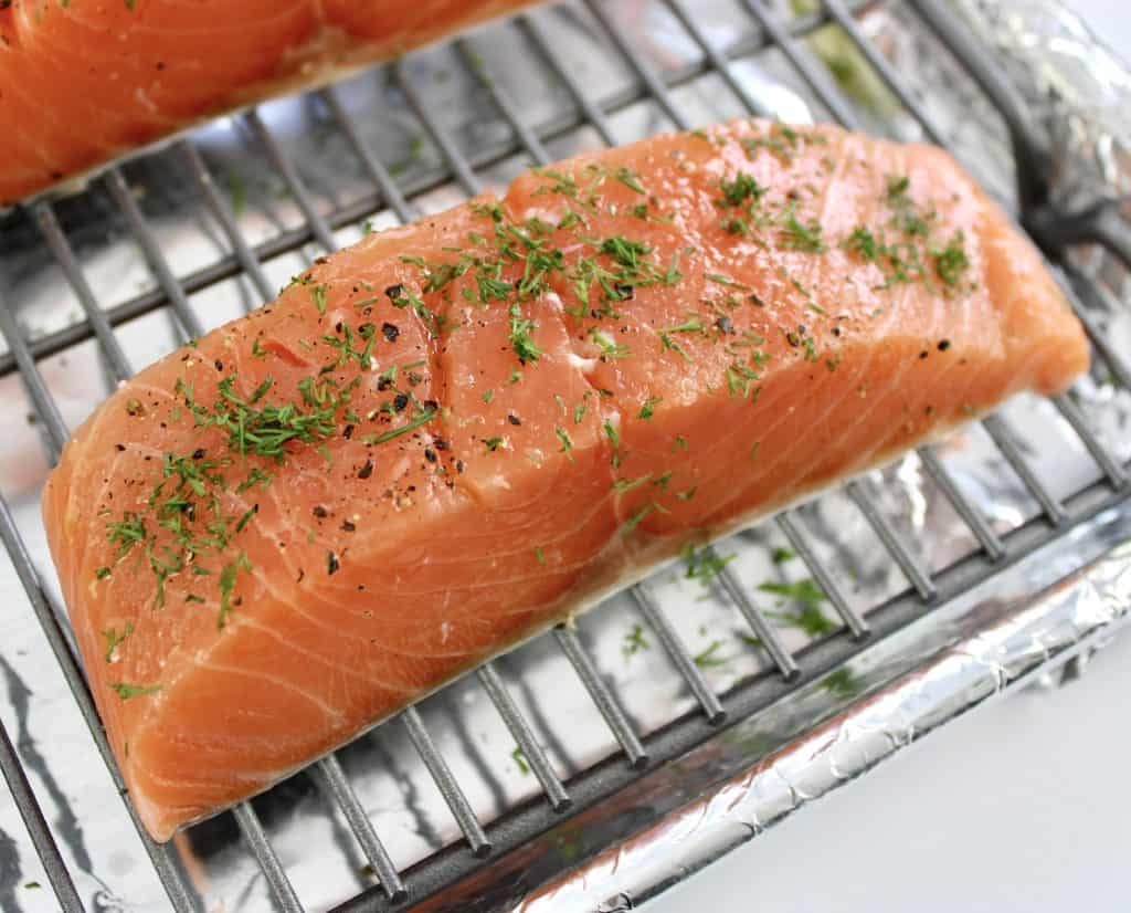 raw salmon slice on baking rack with dill on top