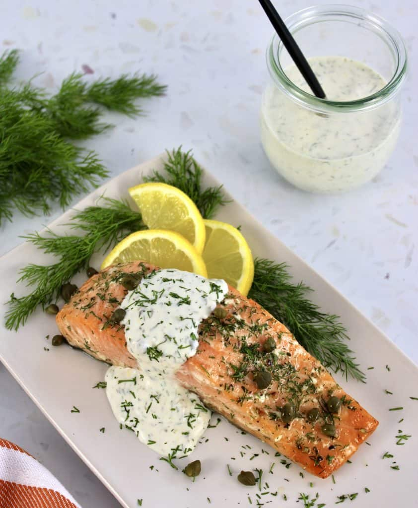 Baked Salmon with Creamy Dill Sauce in background