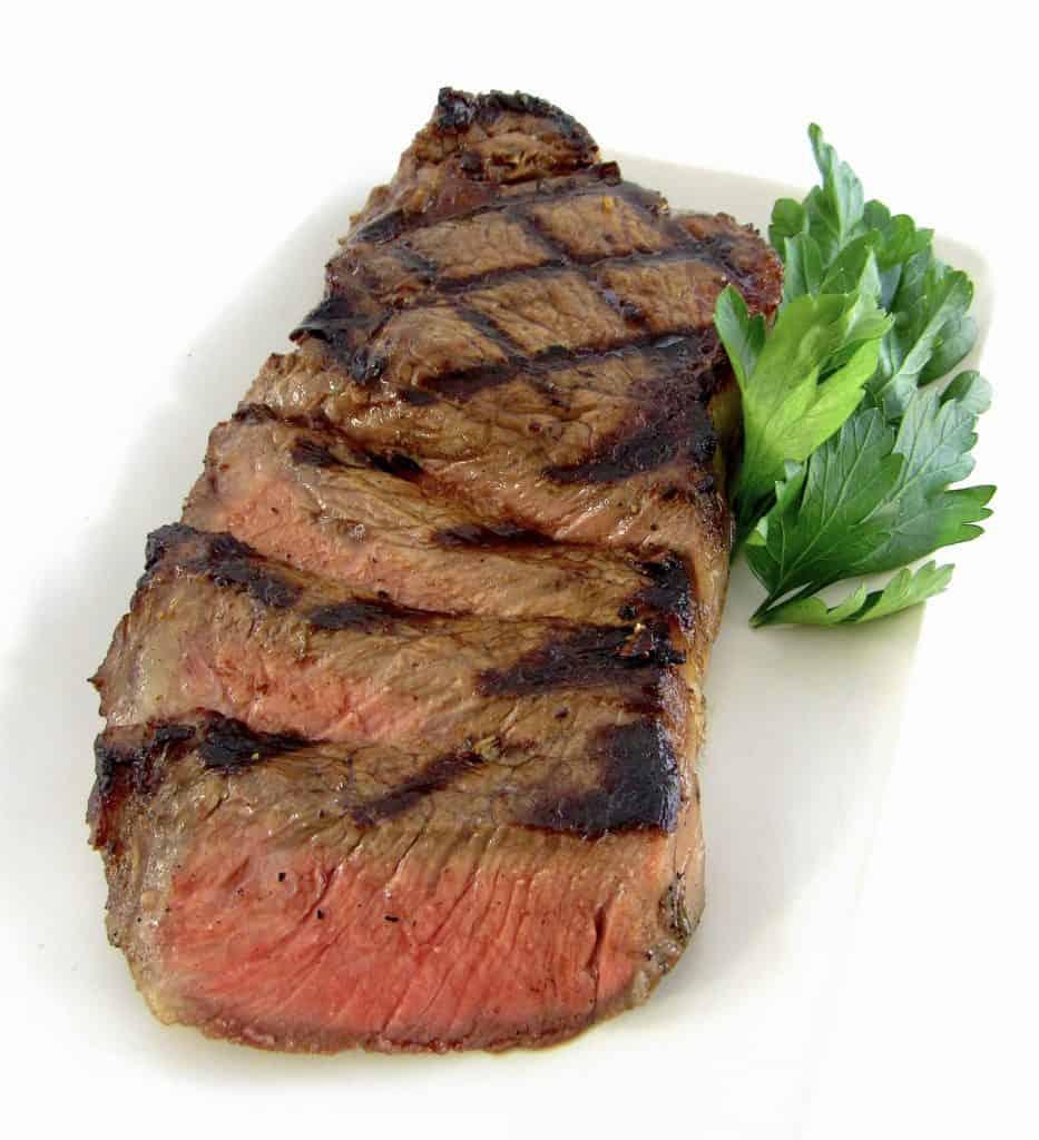 grilled steak sliced on white plate