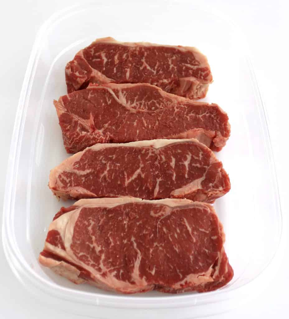 4 NY strip steaks in tupperware container