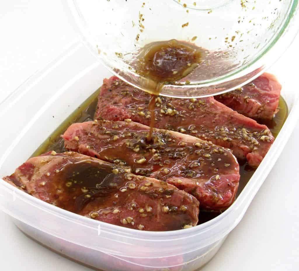 marinade being poured over 4 steaks in tupperware container
