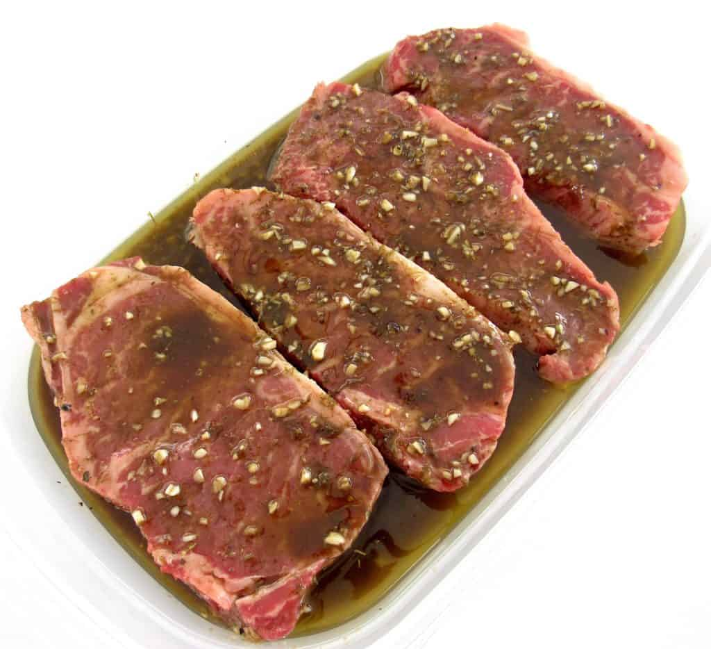 4 steaks in tupperware container with marinade