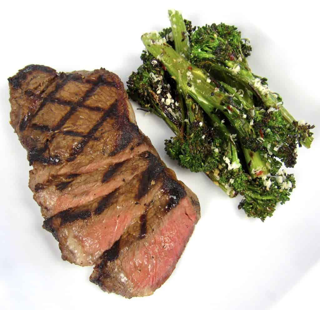 grilled steak sliced and grilled broccolini on side on white plate