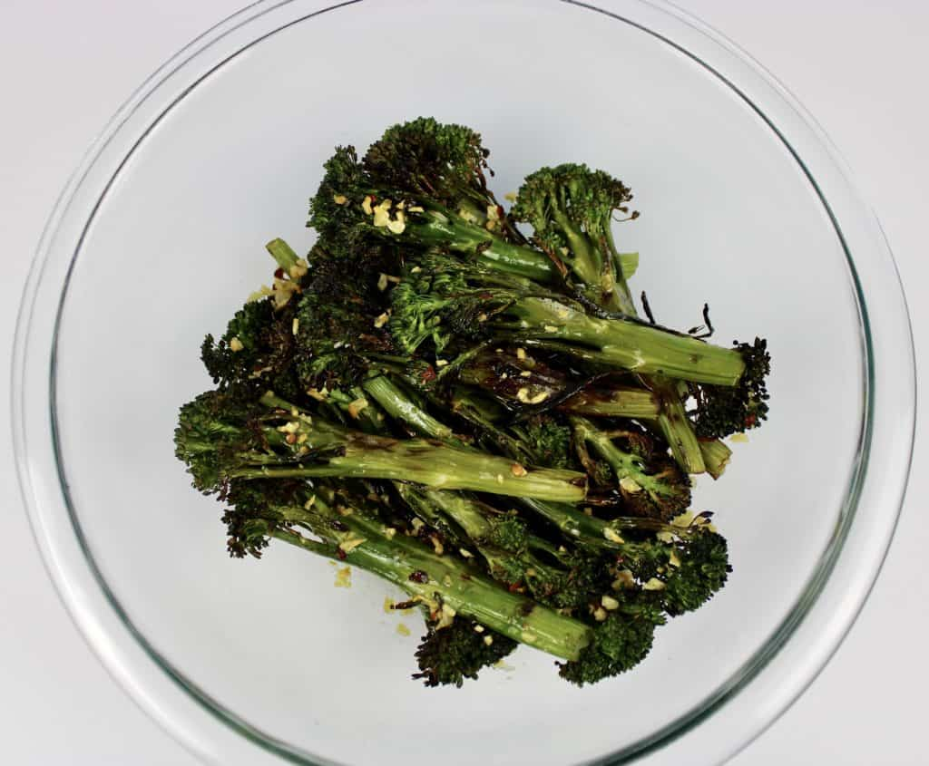 grilled broccolini in glass bowl with garlic butter poured over the top