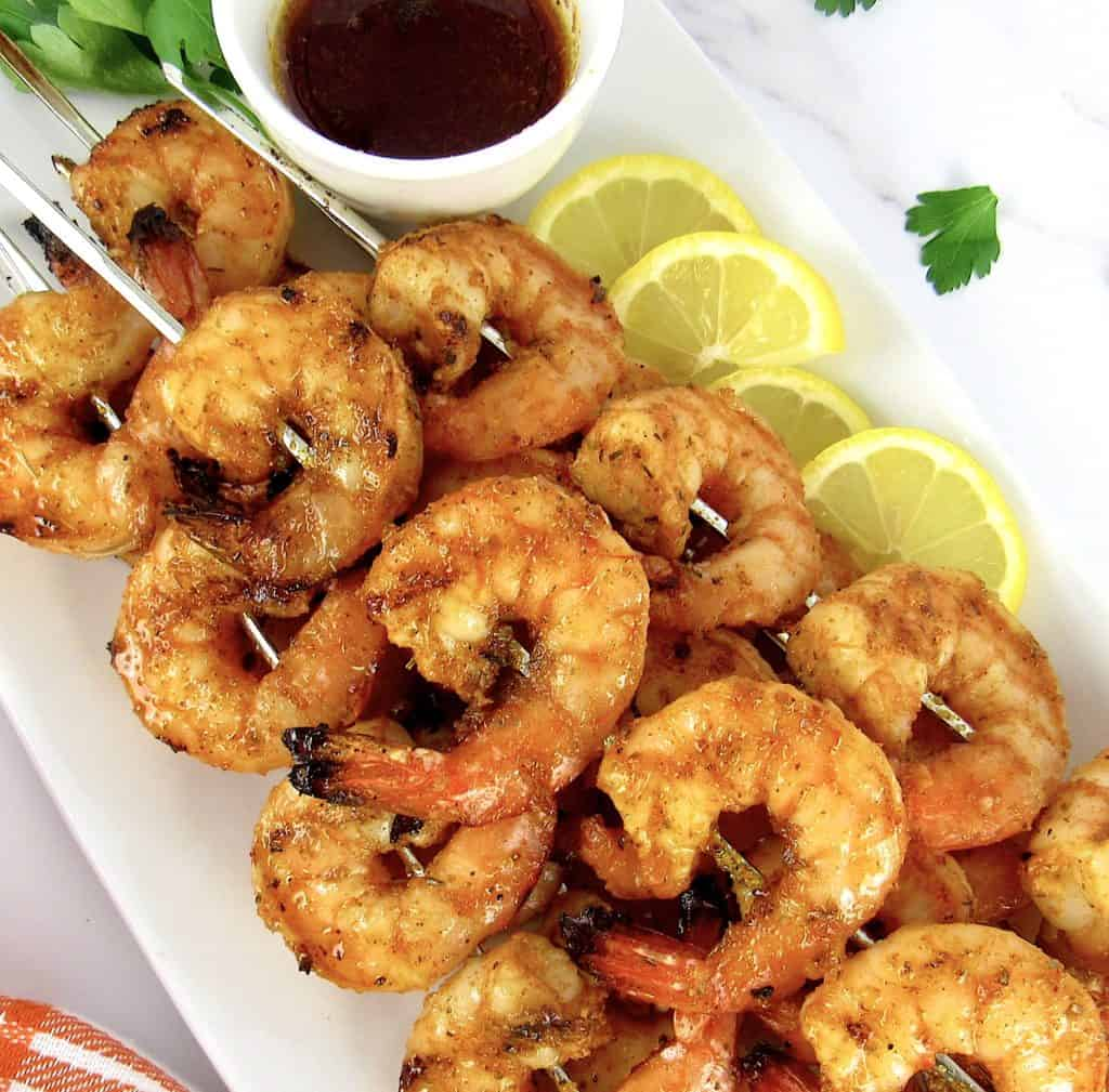 Grilled Cajun Shrimp on white plate with cajun butter on side