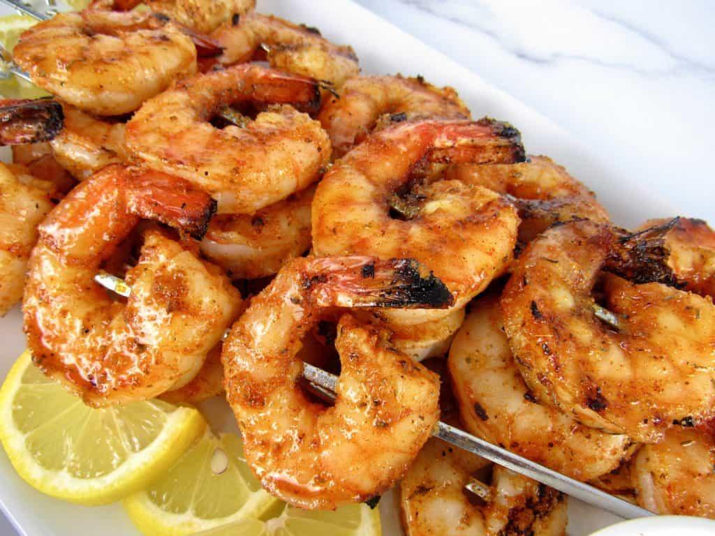 closeup of Grilled Cajun Shrimp skewers on white platter