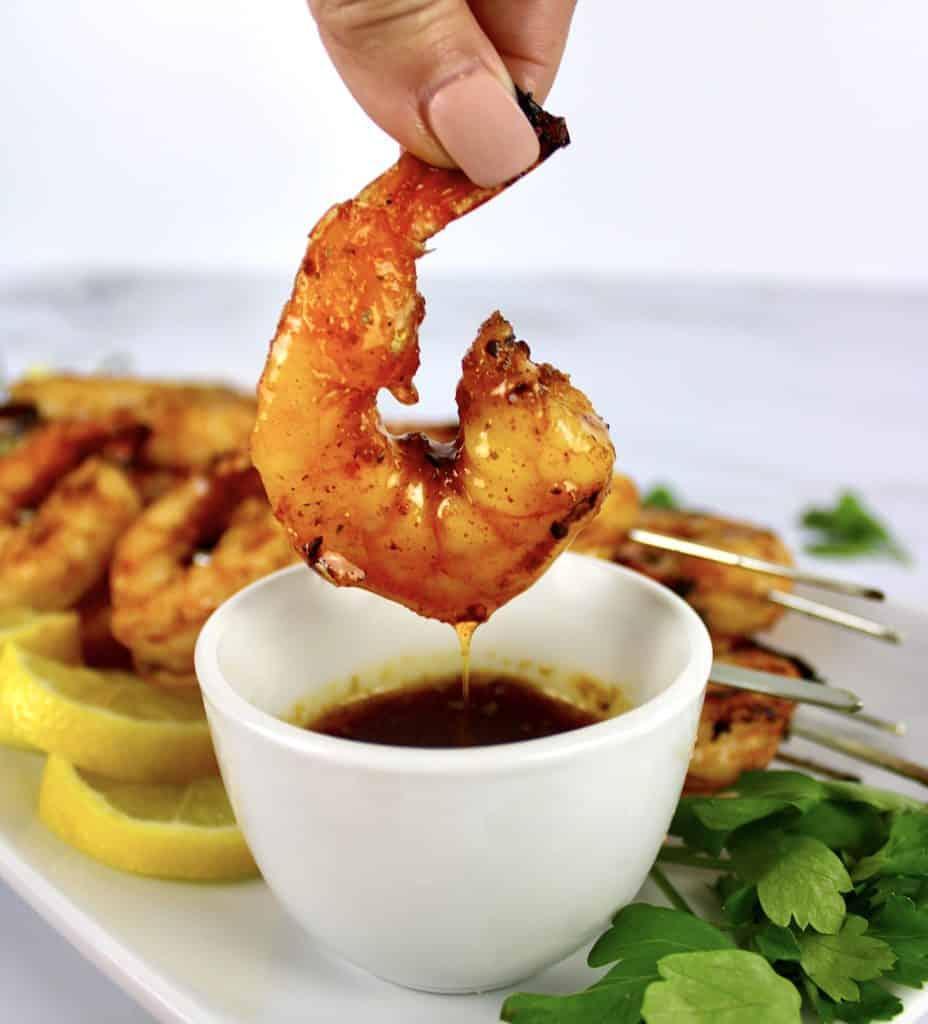 grilled cajun shrimp being dipped into cajun garlic butter