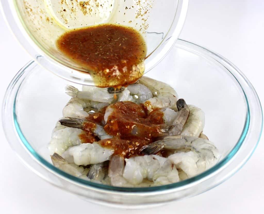 cajun shrimp sauce being poured over shrimp in glass bowl