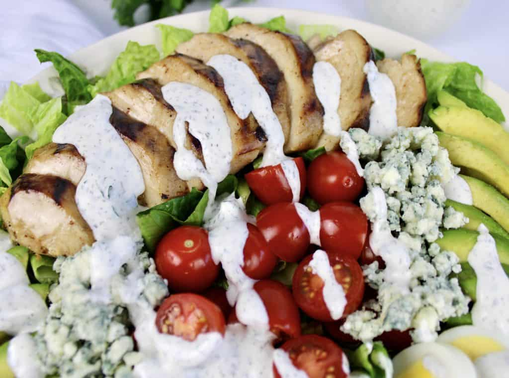 closeup of sliced grilled chicken over salad