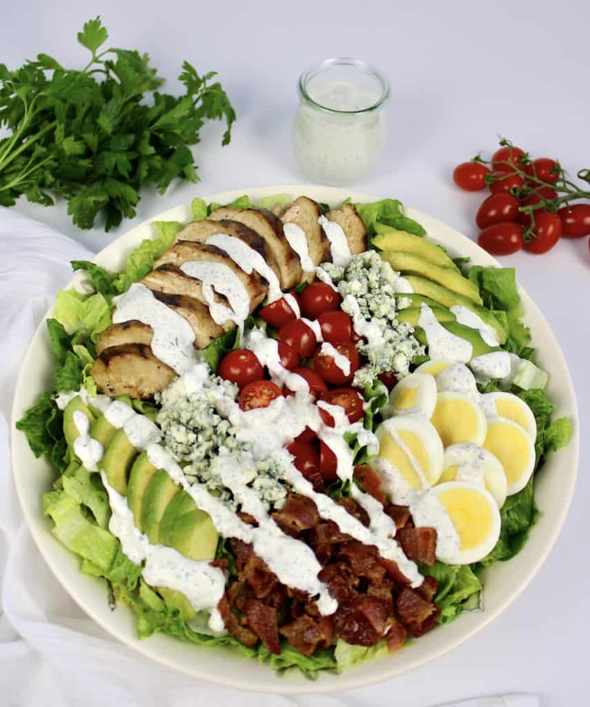 keto cobb salad in large bowl with ranch drizzled on top