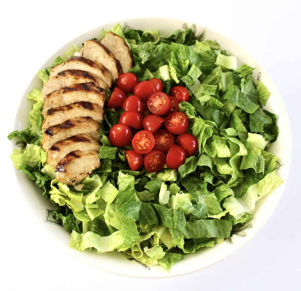 bowl with shredded romaine lettuce with sliced chicken breast on left side and tomatoes in the middle