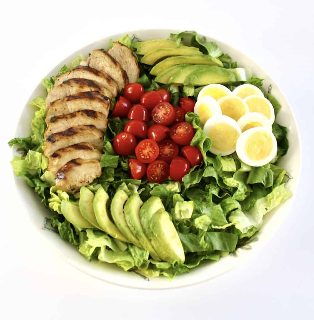 salad in bowl with grilled chicken sliced, egg slices, tomatoes and avocado
