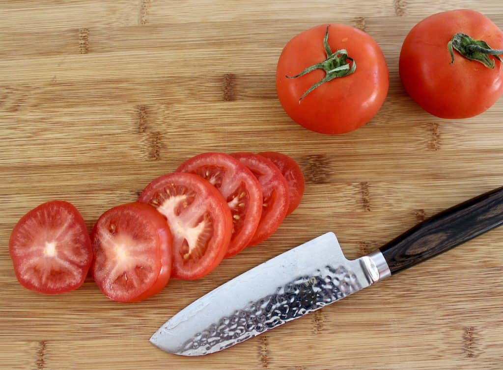 tomatoes sliced on cutting board with knife