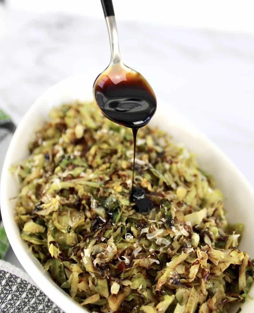 Keto Shredded Brussels Sprouts with balsamic reduction being spooned on top
