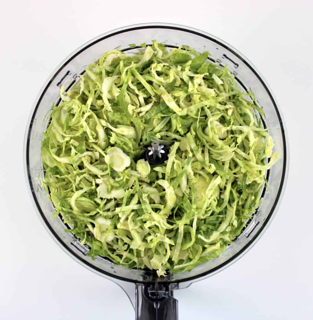 shredded brussels sprouts in bowl of food processor
