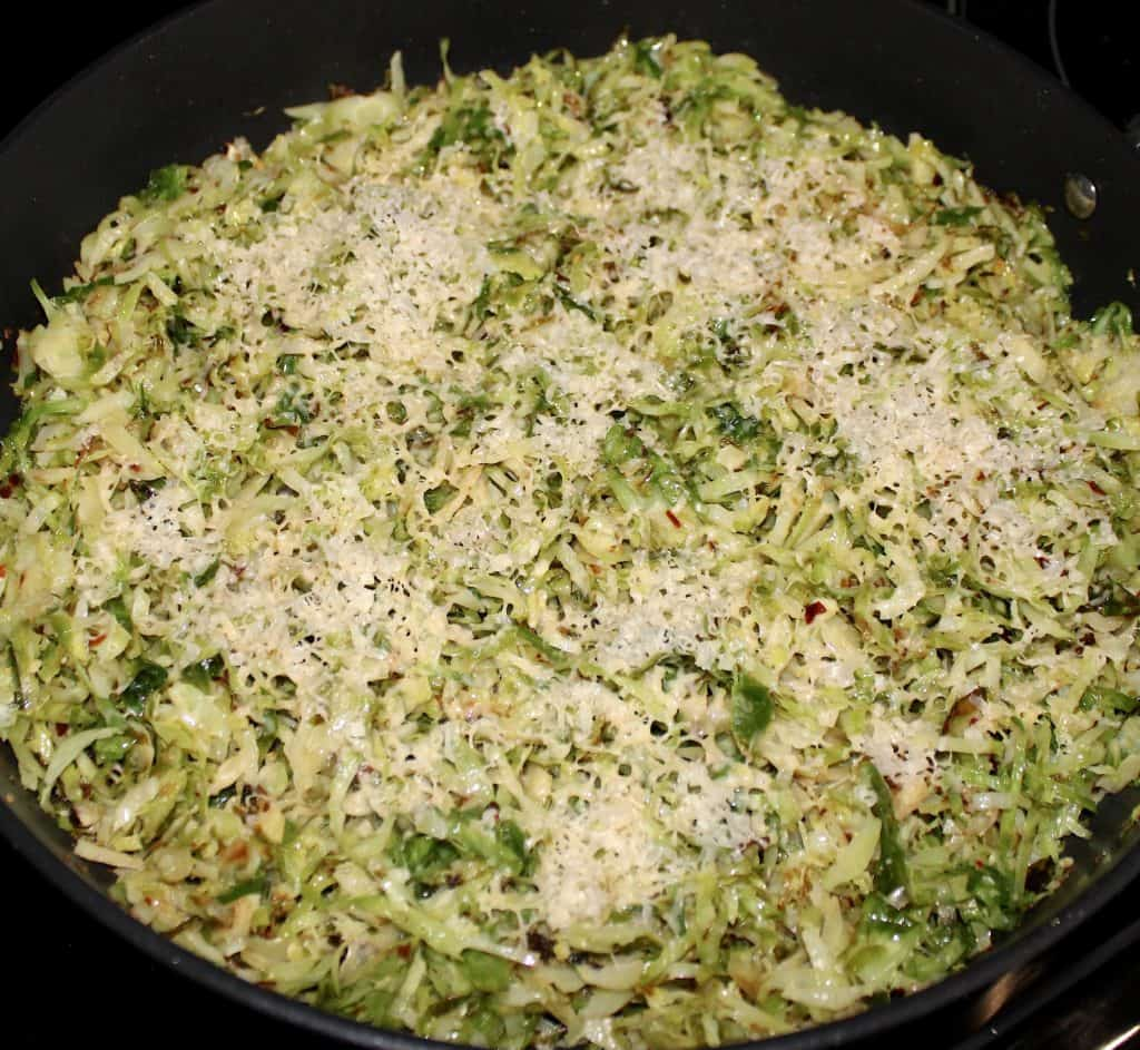 shredded brussels sprouts in skillet with grated cheese on top