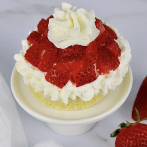 mug cake with whip cream and chopped strawberries on top