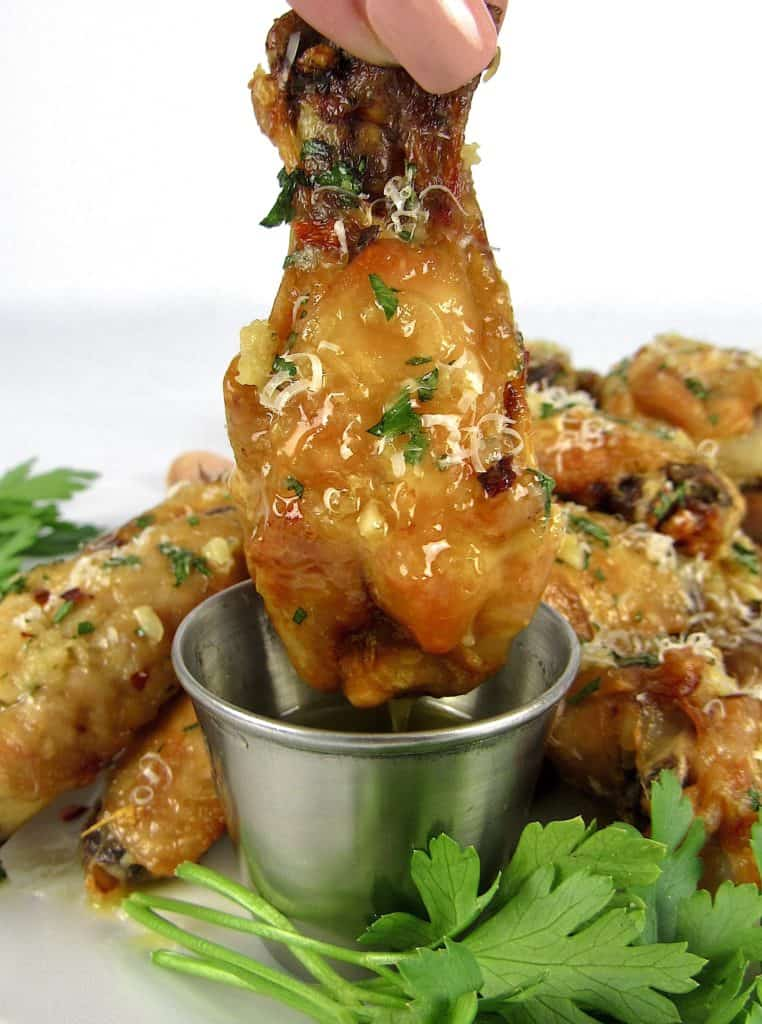 garlic parmesan chicken wing being dipped into melted butter