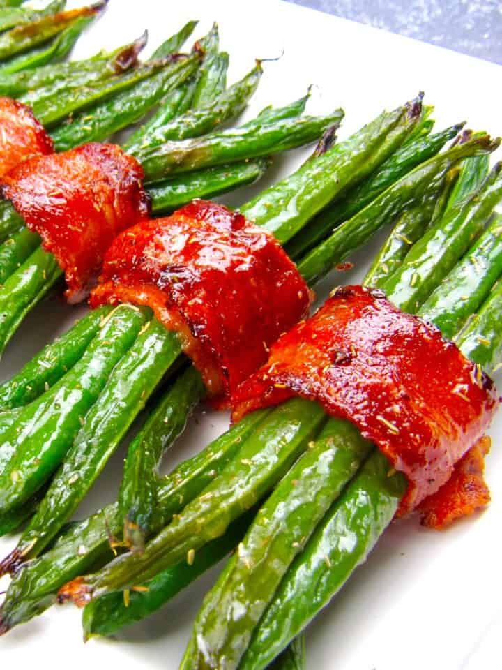 bacon wrapped green beans on white plate running caddy corner