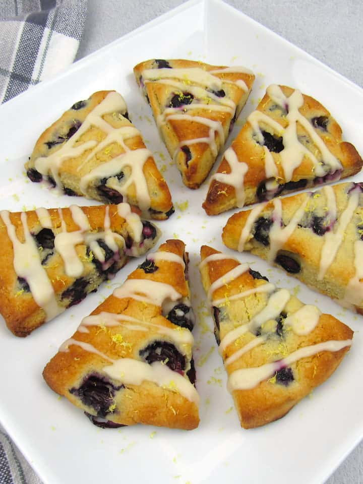 overhead view of 7 blueberry scones with lemon icing drizzle