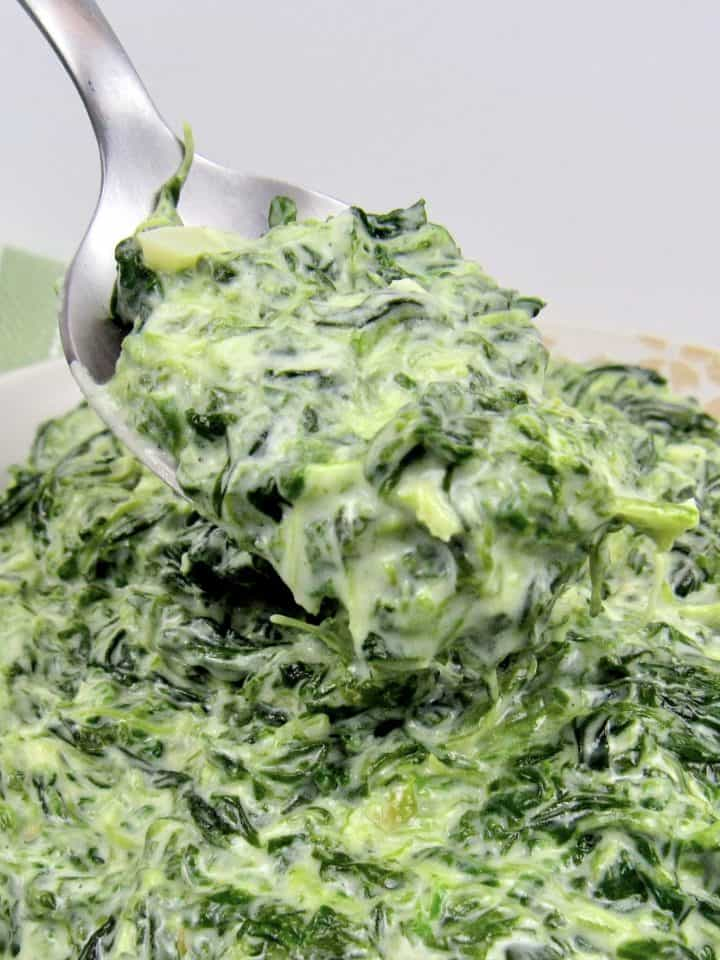 closeup of creamed spinach with spoonful being held up