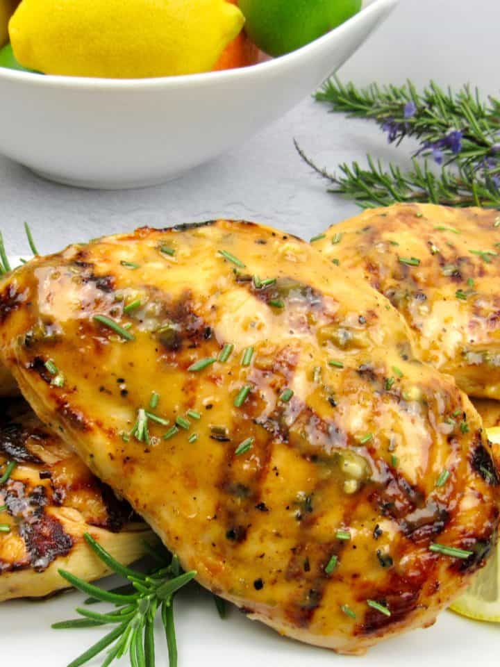 closeup of Grilled Chicken with Rosemary Citrus Glaze on white plate