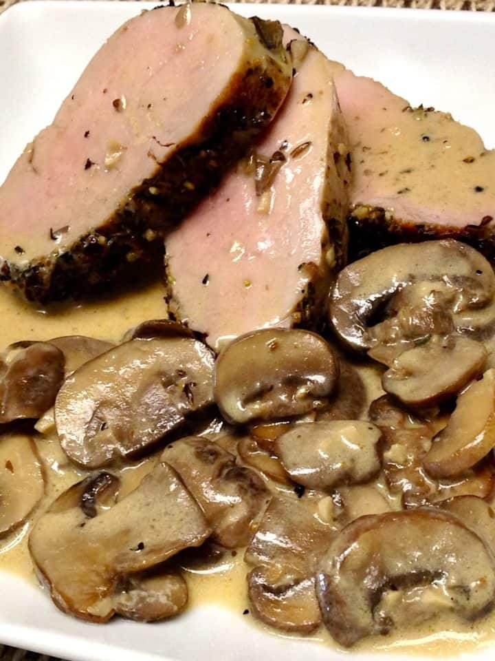 Herb Crusted Pork Tenderloin on white plate with mushrooms on side